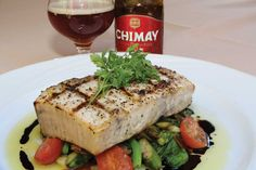 Cut of swordfish on a bed of flash cooked Delta asparagus, pea shoots, spring ramps, cherry tomatoes, olive oil and 100 year old balsamic vinegar, paired with Chimay Première (Red).