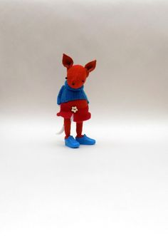 Woollen Fox is handmade by myself using orange woollens and felt.  She is dressed in a blue woolly pullover, white felt pants and a red A line felt skirt.  On her feet she wears blue plastic sneakers.  Stuffed with polyester filling.  Measures - 7 inches tall.  Super sweet Vixen doll for adult or older child.  Thank you for looking.