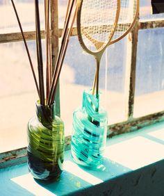 原料に溶かしたガラス端材によってマーブル柄が生まれた吹きガラスの花瓶2個がある窓台