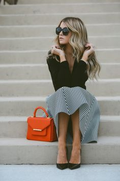 Cara Loren Van Brocklin is wearing a black wrap top, a black and white striped flared midi skirt and black leather pointed pumps.  Skirt: Windsor, Top: Shopbop, Shoes: The Cammeo. Spring Outfits