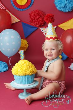 Yellow and blue giant cupcake cake smash photos. love the colors and flowers can be made from crepe paper
