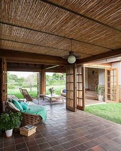 Decoração de casa de campo rústica. Na varanda, porta de madeira, grama, plantas, cadeiras, mesa de centro de madeira, flores. #decoracao #decor #design #details
