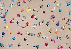 Raggi di sole che brillano sul mare, tavole da surf sull'acqua cristallina e ombrelloni dai colori sgargianti. L'immagine dell'estate sui litorali è sempre magica, ma lo diventa ancora di più se la vista è aerea. Questo è il capolavoro di  Gray Mailin  che, in volo a bord