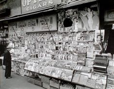 Newsstand, 32nd Street and Third Avenue, Manhattan. Newstand next to State Coffee Shoppe, large display of magazines, ads for sundaes, Coca-Cola above, boxes of sodas below, man at left