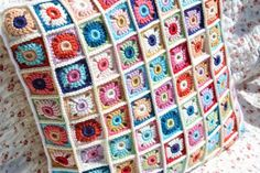 A cushion made of tiny colorful blocks - love the bordered joining method
