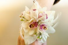 White and pink cymbidium orchids with bling accents, white feathers and a pearl wristlet.