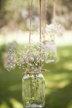 Hanging mason jars wedding ceremony. Baby breath and add pink roses.