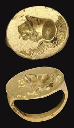 A GREEK GOLD FINGER RING   CLASSICAL PERIOD, CIRCA LATE 5TH-4TH CENTURY B.C.   The plain hoop rounded on the exterior, bevelled on the sides, and flat on the interior, expanding to the slightly off-set oval bezel, engraved with a lion head with a lolling tongue wearing a crested Corinthian helmet