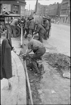 At the scene of the 'incident', telephone repair crews unroll new cables on a bomb damaged London street in order to breach the gap in telephone supply caused by an air raid. Aaron Neville, Alan Turing, Al Capone, Aalborg, Air Raid, Red Army, Lineman, Vietnam Veterans, London Street