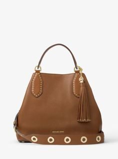 Designed as a go-everywhere style, the Brooklyn shoulder bag takes a bohemian turn for the season, thanks to an expansive silhouette and wide shoulder strap with gleaming grommets. An oversized tassel and soft leather craftsmanship give it tactile richness, while the brand's logo offers a refined nod of signature glamour.