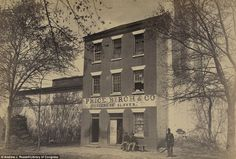 Union army soldiers stand outside Price, Birch and Co, a slave dealer on Duke Street in Alexandria, Virginia. Today the sign on the facade has been removed, but a memorial plaque is positioned in front