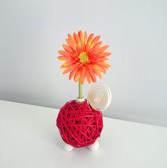 Centro Floral Aromático Flowerfresh modelo Ball. Bola central de color rojo hecha de tiras de ratán. Cuenta con complementos como espiral y mariquita de madera. Además puedes elegir el aroma a evaporar.