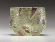 "A ROMAN ""SPLASHED"" GLASS CUP  CIRCA 1ST HALF OF THE 1ST CENTURY A.D.  Transparent pale green in color, free-blown, the surface embellished with applied transparent aubergine and opaque white patches, then further inflated, the biconical body with slightly flanged rim, on a concave base  2 7/8 in. (7.3 cm.) high"