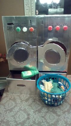 Dramatic play washer and dryer diy out of cardboard boxes and silver duck tape. L is for laundry and laundromat. Featuring Gain laundry detergent and a tiny laundry basket with clothes. Linden