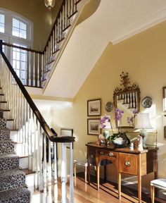 Warm yellow foyer with antique English sideboard and French mirror, and fabulous leopard stair runner complete with brass tread poles (old school, bro) in gorgeous and fancy pants, resorty town Windsor, Florida.