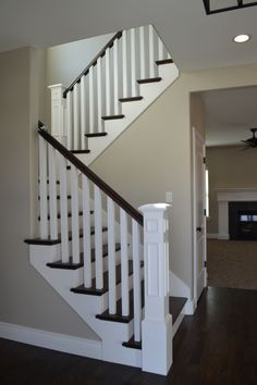 Open railing with hardwood stairs. We love how the dark wood and white painted wood look together!