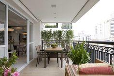 Do outro lado da varanda, que abriga uma mesa de jantar, uma cerca viva de Murta serve para fechar o ambiente e esconder o prédio vizinho.