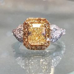 Stunning 2.05 fancy yellow radiant cut diamond surrounded in yellow diamond pave and flanked by pear-shaped diamonds. www.alsonjewelers.com