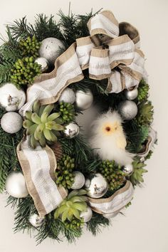 Inventory Sale -----  Christmas wreath with White ribbon.  Using silver color ornaments, pine cones, Artificial succulents and green berries.  It measures approx. 20 diameter.