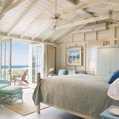 rustic white and blue bedroom overlooking the beach