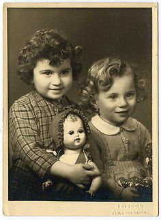 when life was simple and you loved your dolls not your cell phone  Vintage photo of adorable pretty little sisters with curled hair and a big doll.