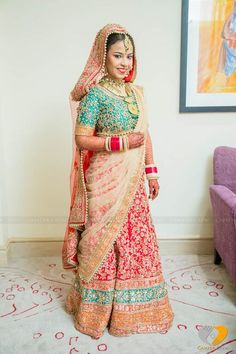 Play with colours on your wedding day like a pro! Take cues from this bride that wore a green blouse, red lehenga and cream dupatta.