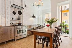Love this combo of modern and clean kitchen, with the rustic / antique table and chairs. (Source: Remodelista)