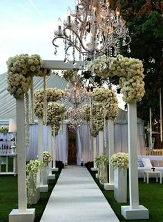 Stunning and dramatic white floral wedding tent entrance by Mark's Garden