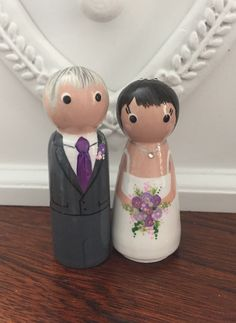 6cm small wooden peg doll wedding cake toppers. Purple flowers on bride and groom