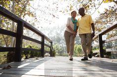Senior couple walking on footbridge in park Stock Photo