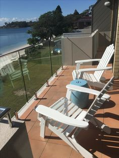 Coastal balcony with new blue ceramic stool as table or seating. Love the colour with the white Adirondack chairs!