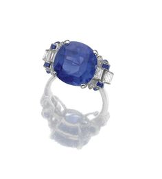 Trendy Diamond Rings : SAPPHIRE AND DIAMOND RING. Claw-set with a cushion-shaped sapphire weighing 9.03