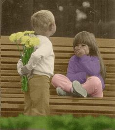 Little girl smiles as little boy tries to hide giving her flowers