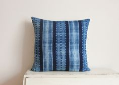 This beautiful cushion cover is made from an African fabric which is fair trade and produce by a small artisan collective. The colours are a mix of light and dark indigo blue with a shibori tie-dyed design. The backing is a plain cream 55% linen and 45% cotton and the cushion closes with a zip at t