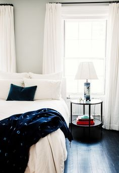 White and navy bedroom with small side table and velvet throw