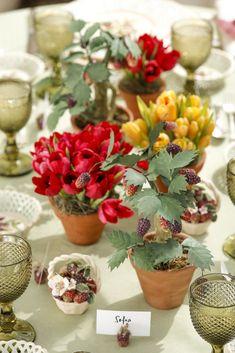 Para florir o centro da mesa, arranjos feitos por Marcio Leme, da Milplantas, com tulipas vermelhas e laranjas plantadas em vasos de barro. Para completar, vasinho com amoras em cerâmica que também faz parte da Coleção Berries.