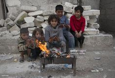 Syrian children heats themselves by a fire in the eastern rebel held Tal Zarzour neighbourhood of the northern Syrian city of Aleppo on November 23, 2014. In recent months, government forces have advanced around the outskirts of the eastern portion of the city that is under rebel control, threatening to encircle it completely.