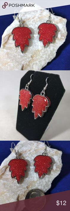 Glittery red leaf earrings These handcrafted leaf shaped epoxy resin earrings are cast with glittering red. They sparkle beautifully in the light. The metal is silver tone alloy. Handmade Jewelry Earrings