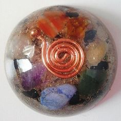CHAKRA BALANCING ORGONITE: Here is the orgonite piece with chakra crystals & many more!Half sphere pendants can also be used as a pocket orgonite or you can place it near your bed or computer. Quartz, sodalite, aventurine, calcite, jaspis, black tourmaline, pyrite, rose quartz, amethyst,Copper spiral,copper BBs,brass,iron& aluminum powder&pieces. All the crystals have been cleared& charged with Reiki energy & 7.83Hz Schumann Resonance.Visit us on…