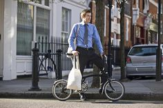 Young businessman with groceries and bicycle