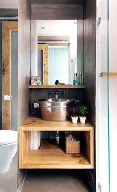 Wood tiles, wood shelves, spa-inspired lighting and a refreshing aqua hue create a resort-like feel in the bathroom.