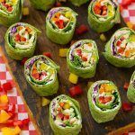 Veggie pinwheels on a board filled with bell peppers, carrots, cabbage and spinach.