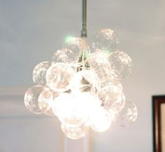 I can't get over how easy and amazing this do-it-yourself chandelier was that Small Notebook created - for only $70. They got the idea from the smart folks at Readymade.    Here's what you need:    18 4-inch glass bubble balls from CB2 ($2 each)  4 cord sets from IKEA ($4 each)  20 gauge floral wire ($1)  fishing line ($1)  galvanized electrical conduit and fittings ($12)  4 25-watt clear bulbs ($1 each)    1. Use scissors to cut the floral wire into 1.5″ lengths, and then bend a small…