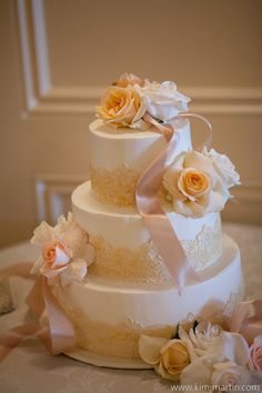 Ivory and champagne buttercream wedding cake with fondant lace and satin ribbon.