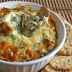 HOT SPINACH & ARTICHOKE DIP:  1/2 (10 oz) pkg frozen chopped spinach, thawed, drained; 1 (14 oz) can artichoke hearts, drained & coarsely chopped; 4 ozs cream cheese, room temperature; 1/2 cup sour cream; 1/4 cup mayo; 1 clove garlic, grated; 1/2 tsp chili sauce (optional); 1/4 cup grated parmigiano reggiano (parmesan), grated; 1/4 cup mozzarella, shredded.
