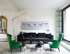 """A modern interpretation of """"The Last Supper"""" hangs above a velvet charcoal sofa in the chic living room of the home of Cendrine Dominguez, featured in Marie Claire Maison."""