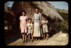 Barefoot mother and children, two with shoes, outside thatched house by t13hman, via Flickr