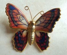 A pretty vintage multicoloured enamel butterfly brooch. The brooch design is of a multicoloured butterfly with red, pink and green tones set on gold tone metal,  with a gold tone body and gold wire antennae.  Vintage circa 1980's
