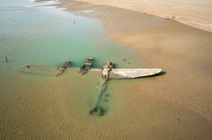 Sixty-five years after it crash-landed on a beach in Wales, an American P-38 fighter plane has emerged from the surf and sand where it lay buried