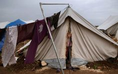 A young Syrian girl looks out of a tent at a Syrian refugee camp. www.narenjtree.org